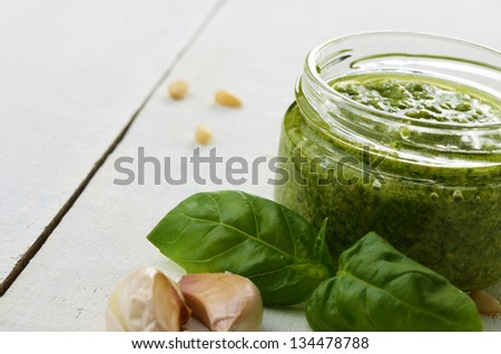 Glass jar of pesto sauce on white kitchen table with copy-space - stock photo