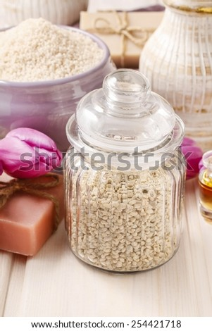 Glass jar of sea salt on white wooden table, tulip flowers in the background