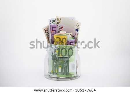 Glass Jar Overflowing With Euro Bills (has clipping path) - stock photo