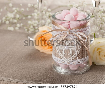 Glass jar with candies and roses on the tablecloth - stock photo