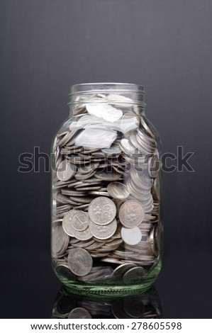Glass jar with coin isolated on black background                              - stock photo