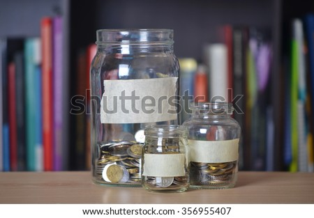 Glass jar with coin on blur bookshelf background