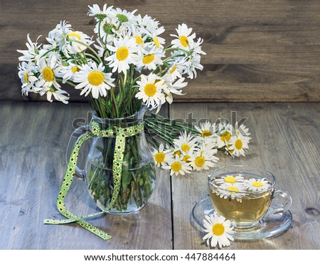 Glass jar with daisies and a cup of green tea. Bouquet of daisies lying on the wooden background.