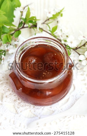 Glass jar with fig jam on a white wooden table with flowers, selective focus - stock photo