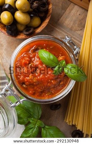 Glass jar with homemade classic spicy tomato pasta or pizza sauce with olives and basil. Italian healthy food background. - stock photo