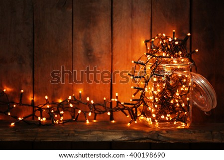 Glass jar with lighted garland on wooden background - stock photo