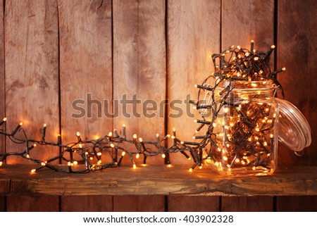 Glass jar with lighted garland on wooden background