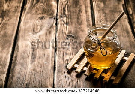 Glass jar with natural honey and a spoon. On wooden background.