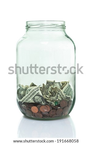 Glass jar with some money in the bottom - stock photo