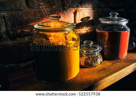 Glass jars filled with spices on a wooden shelf