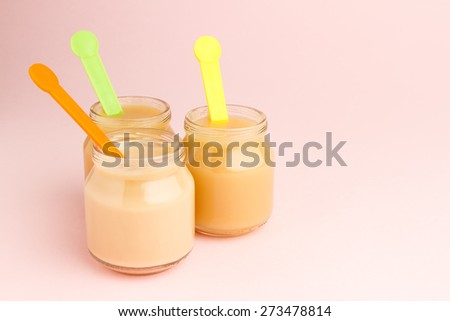 Glass jars of baby food with colorful spoons on pink background with copy space - stock photo