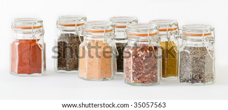 Glass jars of herbs and spices in a row on white background