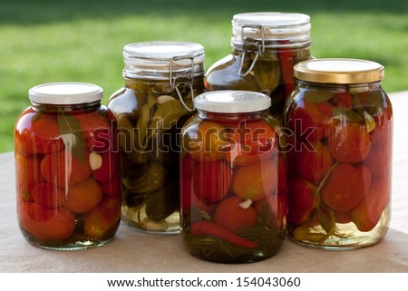 Glass jars of homemade canned tomatoes and cucumbers on the outdoors kitchen