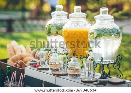 Glass jars of lemonade on wedding candy bar - stock photo