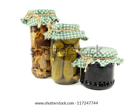Glass jars of preserved mushrooms, pickled cucumbers and jam on a white background - stock photo