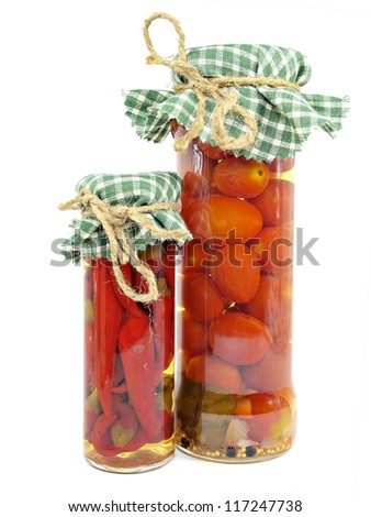 Glass jars of preserved tomatoes and red hot peppers on a white background - stock photo