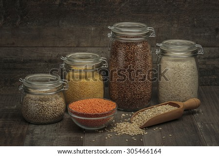 Glass Jars with Buckwheat, millet, barley, lens, and rice on a wood - stock photo