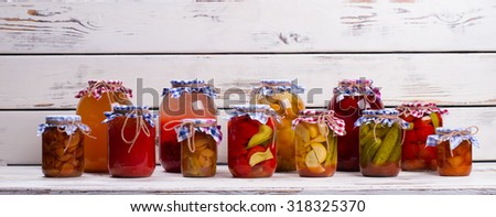 Glass jars with canned vegetables and fruits on a wooden shelf. Canned foods. - stock photo