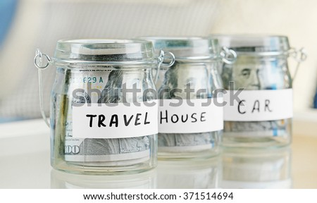 Glass jars with dollar banknotes for car, house and travel on a table - stock photo