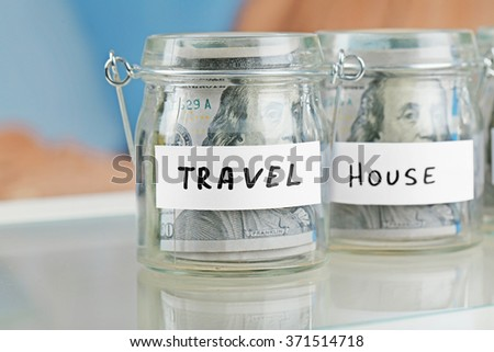 Glass jars with dollar banknotes for house and travel on a table - stock photo
