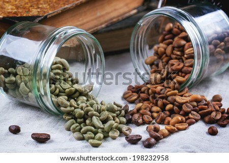 Glass jars with green and brown decaf unroasted coffee beans on tablecloth - stock photo