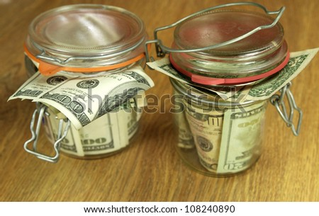 glass jars with money on the wooden table