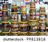 glass jars with nuts and honey on display in a store in the background - stock photo