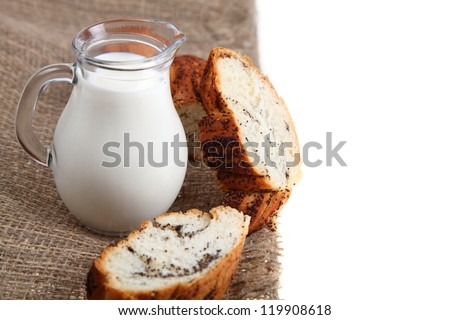 Glass jug with milk and bread on a brown fabric on a white background