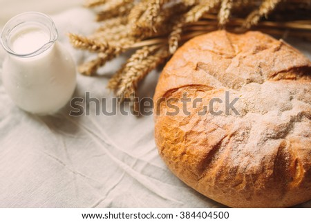 Glass jug with milk and bread on white textile