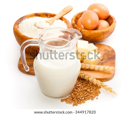 Glass jug with milk, wheat seeds, flour and two eggs on white background - stock photo