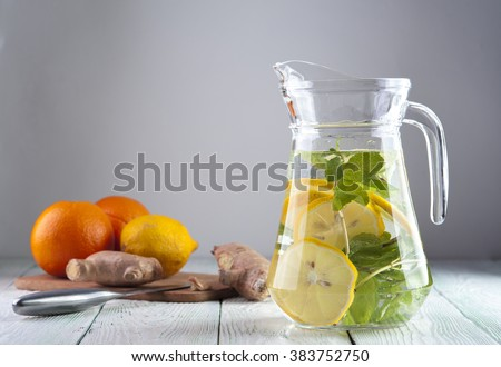 Glass jug with mineral water, lemon slices and mint on the background of lemon, orange and ginger on wooden table. Drink for diet. Focus on jug. - stock photo