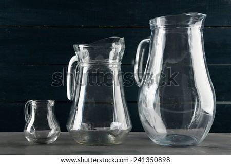 Glass jugs on dark color wooden background - stock photo