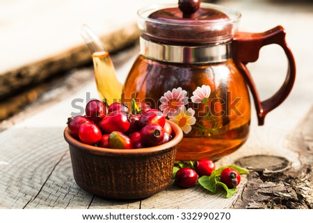 Glass kettle with tea and bowl with berry of a dogrose - stock photo