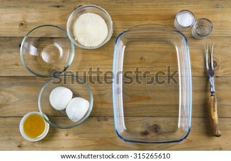 glass kitchenware on wooden background: baking tray and bowls - stock photo
