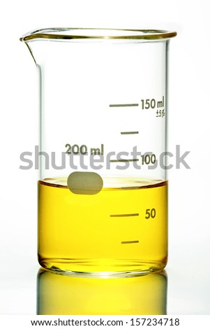 Glass laboratory beaker with yellow liquid on white background. - stock photo