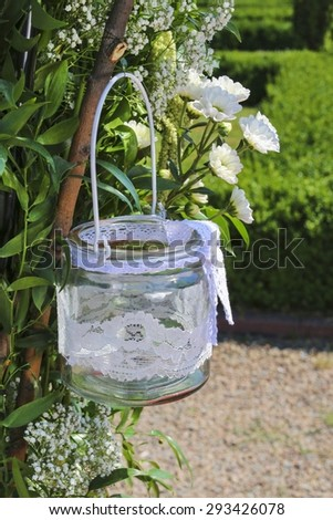Glass lantern decorated with white lace hanging on wedding archway. - stock photo