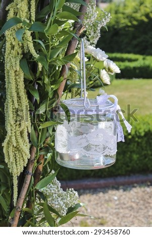 Glass lantern decorated with white lace hanging on wedding archway.
