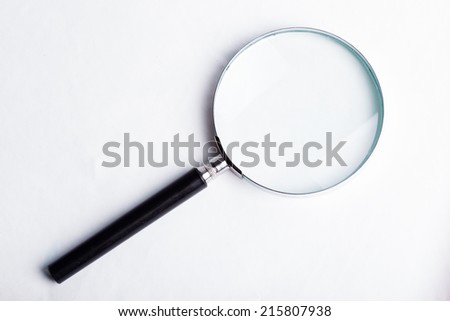 Glass magnifier closeup on blue background - stock photo