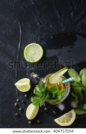 Glass mason jar of Ice green tea with lime, lemon, mint and ice cubes on black slate stone board over black textured background. Flat lay. With copy space. Focus on mint - stock photo