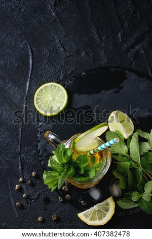 Glass mason jar of Ice green tea with lime, lemon, mint and ice cubes on black slate stone board over black textured background. Flat lay. With copy space