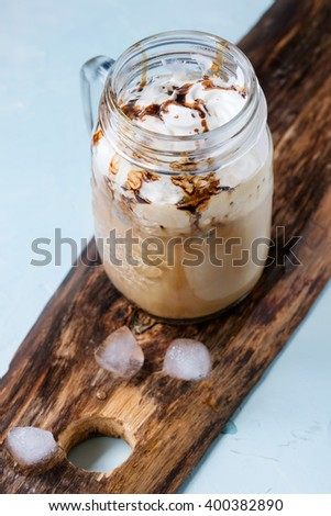 Glass mason jar with ice coffee with whipped cream, ice cream and chocolate sauce, served with coffee beans and ice cubes on wooden chopping board over light blue textured background. - stock photo