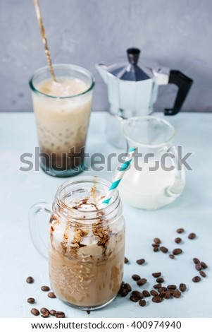 Glass mason jar with ice coffee with whipped cream, ice cream and chocolate sauce, served with coffee beans, coffee pot and jug of milk over light blue textured background. - stock photo