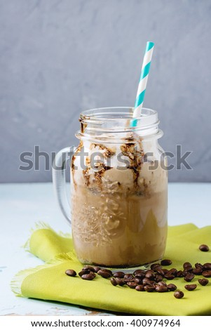 Glass mason jar with ice coffee with whipped cream, ice cream and chocolate sauce, served with coffee beans and ice cubes on green textile napkin over light blue textured background. - stock photo