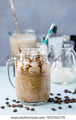 Glass mason jar with ice coffee with whipped cream, ice cream and chocolate sauce, served with coffee beans, coffe pot and jug of milk over light blue textured background.