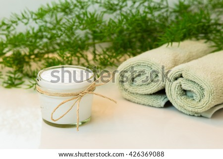 Glass mason jar with white cream, decorated with twine bow. Rolled green towels in a spa setting. Green plant decor in background. Bathroom white countertop. - stock photo