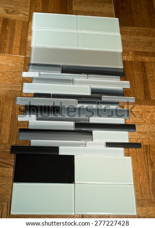 glass mosaic tile and subway tile for kitchen backsplash walls and other interior spaces against parquet flooring - stock photo
