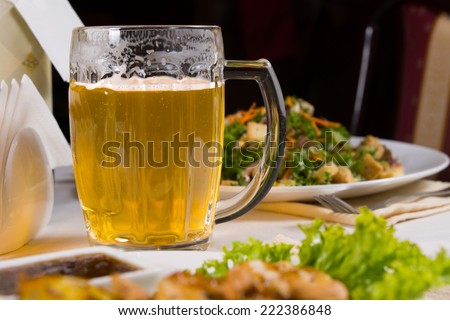 Glass Mug of Beer on Table Amongst Plates of Food on Table in Restaurant - stock photo