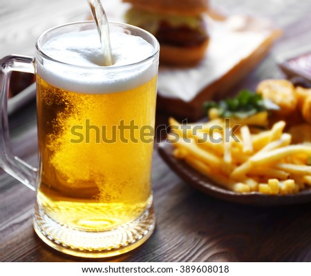 Glass mug of draft light beer with French fries on dark wooden table, close up - stock photo