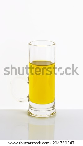 glass mug of fresh olive oil on white table
