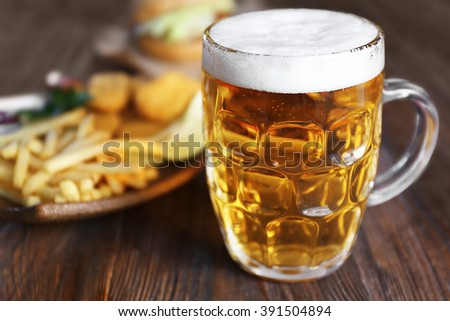 Glass mug of light beer with French fries on dark wooden table, close up